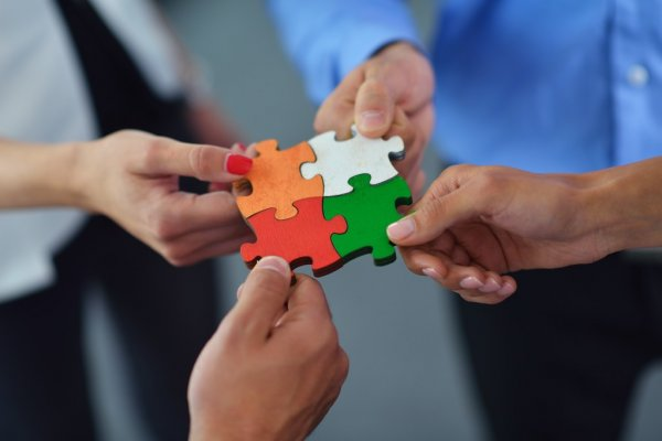 Group of business people assembling jigsaw puzzle — стоковое фото